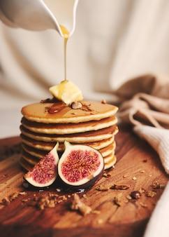 Vertikale aufnahme von pfannkuchen mit sirup, butter und gerösteten nüssen auf einem holzteller