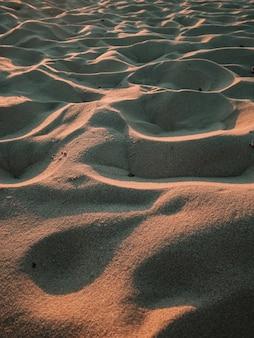 Vertikale aufnahme von sandtextur in einem wellenmodus an der küste des meeres