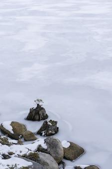 Vertikale aufnahme von schneebedeckten felsen im gefrorenen wasser