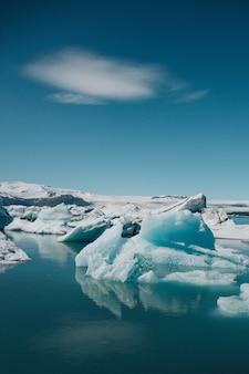 Vertikale aufnahme von schönen eisbergen auf dem ozean, der in island gefangen genommen wird