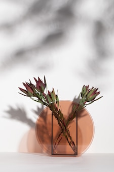 Vertikale aufnahme von schönen roten billbergia-blumen in einer glasvase