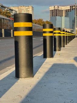Vertikale aufnahme von schwarzen zaunpollern, die den bürgersteig vor autos schützen