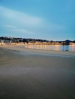 Vertikale aufnahme von stadtlichtern, die im ozean in san sebastian, spanien reflektieren