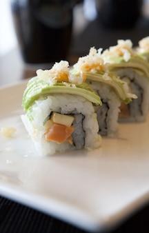 Vertikale aufnahme von sushi-rollen auf einem teller auf dem tisch