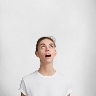 Vertikale aufnahme von überraschten schockierten schönen weiblichen blicken mit unerwartetem ausdruck nach oben, lokalisiert über weißem hintergrund. entzückende junge hübsche frauenmodelle allein im studio. gesichtsausdrücke