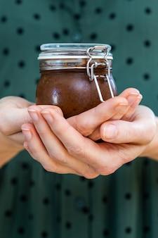 Vertikale aufnahme von weiblichen händen, die eine hausgemachte vegane rohe pflaumenmarmelade in einem glas halten