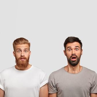 Vertikale aufnahme von zwei überraschten männern mit dicken stoppeln, wunder der neuesten nachrichten über freund, offene augen weit offen, schulter an schulter stehend, isoliert über weißer wand, gekleidet in lässigen t-shirts