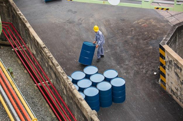 Vertikale bewegung der ölfässer von oben für die männliche arbeiterhilfe beim arrangieren.