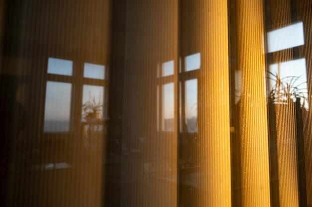 Vertikale breite jalousien vor dem fenster im licht des sonnenuntergangs, ein spiegelbild von bürofenstern.