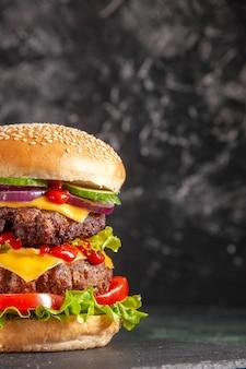 Vertikale des köstlichen fleischsandwiches mit tomatengrün auf dunklem farbtablett auf schwarzer oberfläche