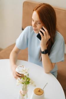 Vertikale draufsicht der glücklichen jungen frau, die tasse mit heißem kaffee in den händen hält und am handy spricht, das am schreibtisch im café sitzt. kaukasische dame der hübschen rothaarigen, die freizeitbeschäftigung im café hat.