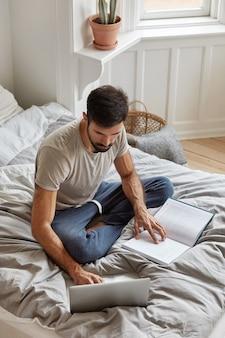Vertikale draufsicht des beschäftigten unrasierten kerls, der beschäftigt ist, kursarbeit zu machen, literatur studiert und am lapop-computer arbeitet