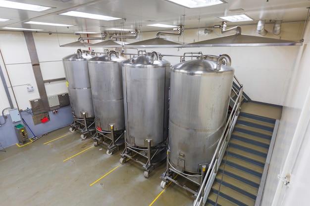 Vertikale edelstahltanks mit druckmesser im gerätetank chemiekeller bei der reinigung und behandlung von edelstahltanks mit scrollrad in der shampooanlage