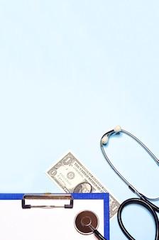 Vertikale flach gelegte bezahlte medizin, bestechung zur behandlung. stethoskop auf einem dollar- und papierformular. draufsicht, kopie, raum