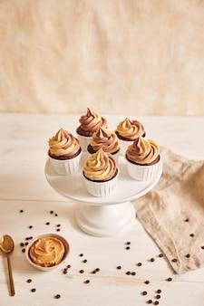 Vertikale flache fokus-nahaufnahmeaufnahme von köstlichen erdnussbutter-cupcakes mit cremiger glasur