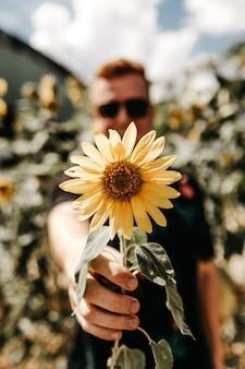 Vertikale flache fokussierte aufnahme eines mannes, der eine gelbe sonnenblume hält