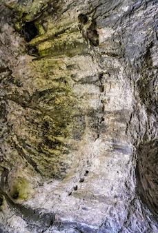 Vertikale flachwinkelaufnahme der schönen steinmauern, die mit moos in einer natürlichen höhle bedeckt sind