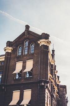 Vertikale flachwinkelaufnahme eines braunen und beigen gebäudes unter einem klaren himmel
