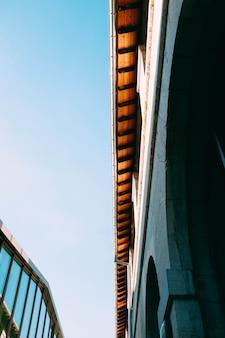 Vertikale flachwinkelaufnahme eines grauen betongebäudes vor einem gebäude mit glasfassade