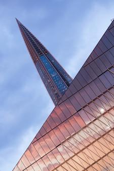 Vertikale flachwinkelaufnahme eines laktha-zentrums, das den sonnenuntergang in russland reflektiert