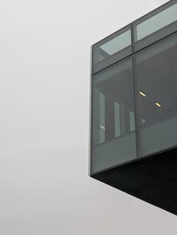 Vertikale flachwinkelaufnahme eines schwarzen hochhausgebäudes mit glasfenstern