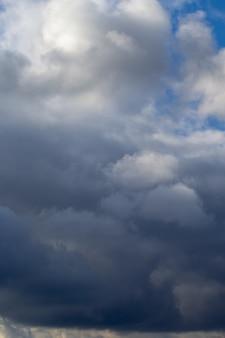 Vertikale. gewitterwolken wolken am blauen himmel. grauweiße wolken. frühlingstag. schöner naturhintergrund.