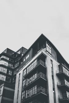 Vertikale graustufenaufnahme eines architektonischen gebäudes mit balkonen