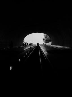 Vertikale graustufenaufnahme eines durchgangs in einem tunnel - ideal für einen monochromen hintergrund