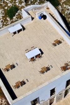 Vertikale hochwinkelaufnahme eines cafés auf dem dach eines hellblauen gebäudes