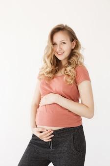 Vertikale küste der glücklichen blonden jungen mutter mit langen haaren in der sportkleidung, die hell lächelt und schwangeren bauch mit den händen berührt