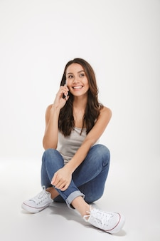 Vertikale lächelnde brunettefrau, die auf dem boden sitzt und durch smartphone über grau spricht