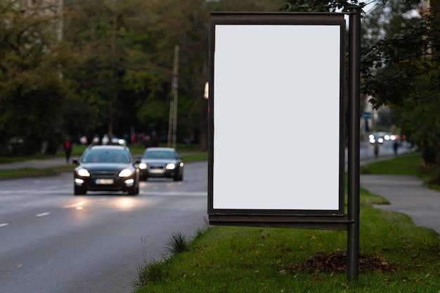 Vertikale leere plakatwand auf der stadtstraße, in der oberfläche die defokussierte abendstraße mit autos