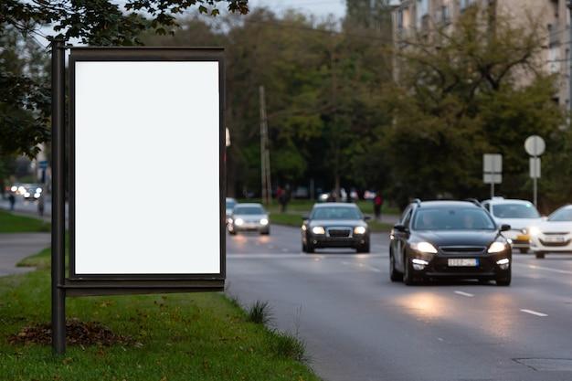 Vertikale leere plakatwand auf der stadtstraße, in der wand die defokussierte abendstraße mit autos