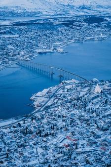 Vertikale luftaufnahme der schönen stadt von tromso bedeckt mit schnee, der in norwegen gefangen genommen wird