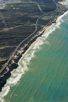 Vertikale luftaufnahme einer straße in der mitte von grasfeldern nahe einem strandufer