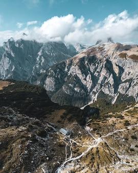 Vertikale luftaufnahme von bergen unter blauem himmel und weißen wolken