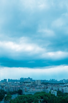 Vertikale luftaufnahme von hohen stadtgebäuden unter einem bewölkten hellblauen himmel