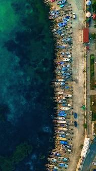 Vertikale luftaufnahme von verschiedenen booten, die am rand des ufers nahe dem wasser geparkt werden