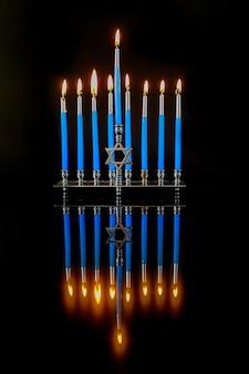 Vertikale menora mit blauen brennenden kerzen und reflexion auf oberfläche für chanukka jüdischen feiertag.