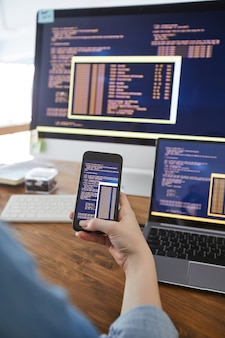 Vertikale nahaufnahme der weiblichen hand, die smartphone mit code auf dem bildschirm beim arbeiten am schreibtisch im büro hält, weibliches it-entwicklerkonzept, kopienraum