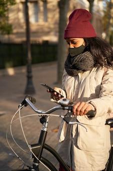 Vertikale nahaufnahme einer jungen frau auf ihrem fahrrad unter verwendung ihres smartphones. sie trägt winterkleidung und ist in einer stadt mit herbstwetter.