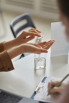 Vertikale nahaufnahme einer nicht erkennbaren frau, die in der arztpraxis händedesinfektionsmittel verwendet, platz kopieren