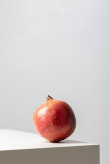 Vertikale nahaufnahme eines granatapfels auf dem tisch unter den lichtern auf weiß