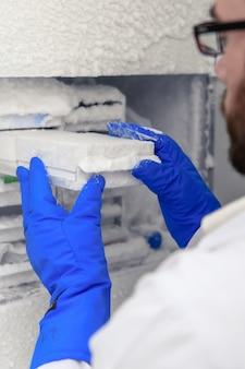 Vertikale nahaufnahme eines laboranten, der koronavirusproben inkubiert