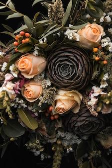 Vertikale nahaufnahme eines luxuriösen straußes von orangefarbenen und braunen rosen