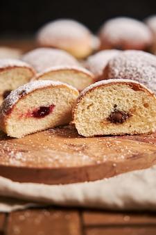 Vertikale nahaufnahme von flauschigen donuts gefüllt mit marmelade auf einem tablett auf dem tisch unter den lichtern