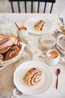 Vertikale nahaufnahme von leckeren nussschnecken mit kaffee-cappuccino auf dem weißen holztisch