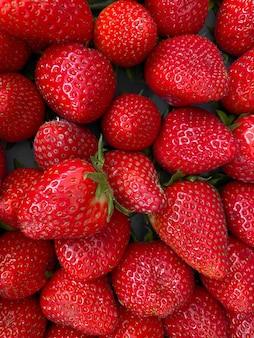 Vertikale nahaufnahme von leuchtend roten saftigen frischen erdbeeren