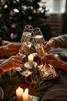 Vertikale nahaufnahme von vier personen, die zusammen weihnachtsessen genießen und mit champagnerglas anstoßen...