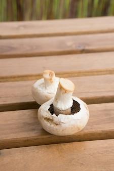 Vertikale nahaufnahme von zwei frischen pilzen auf einer hölzernen tischoberfläche